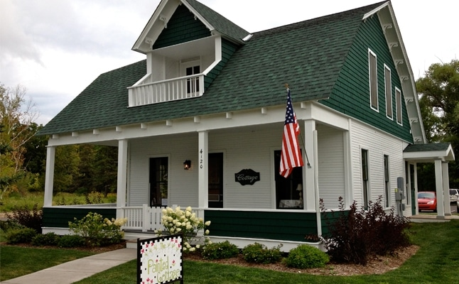 The painted cottage one of two historic homes moved into town sells
