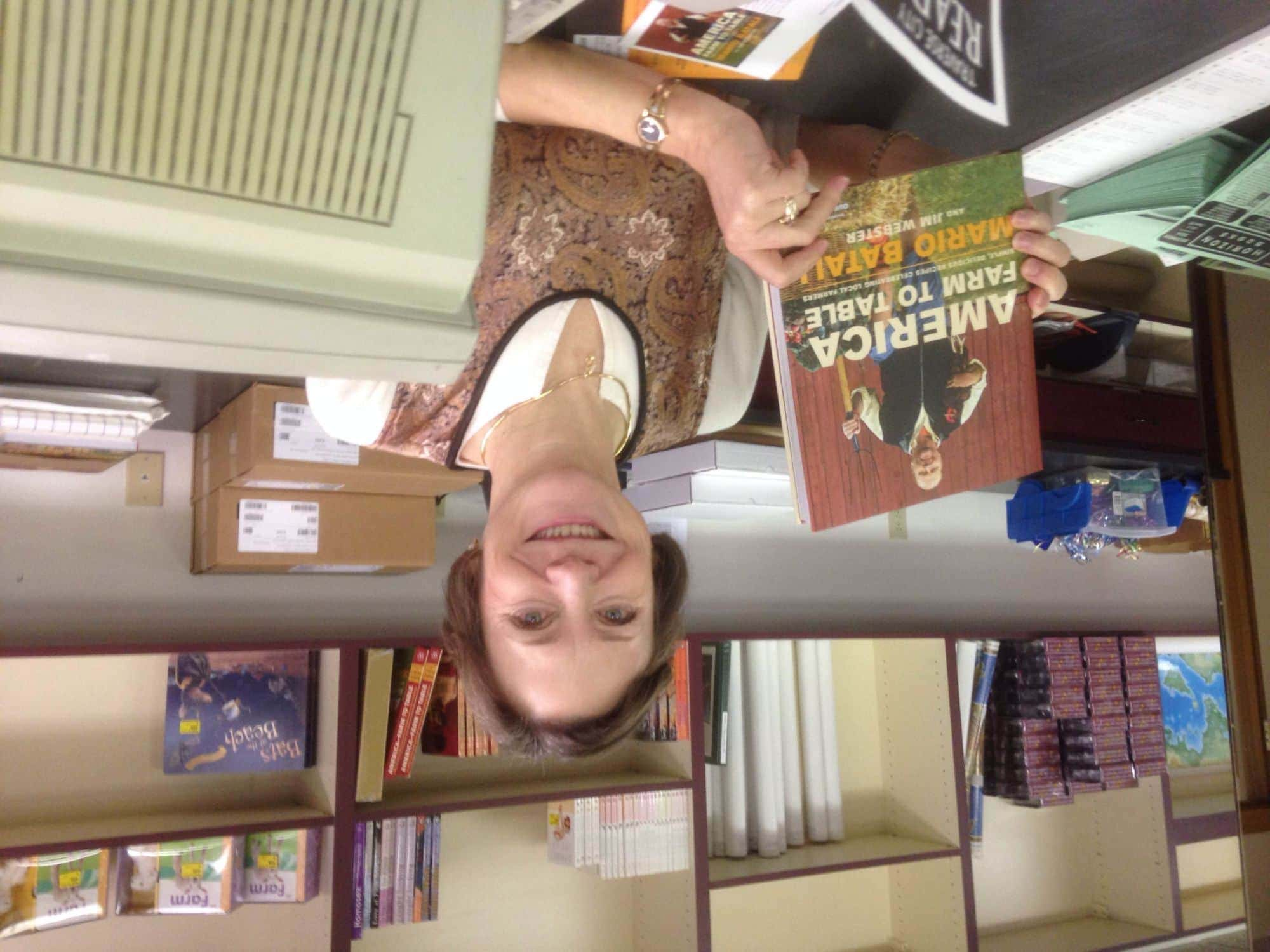 Amy Reynolds of Horizon Books shows off a copy of Mario Batali's latest cookbook, America Farm to Table