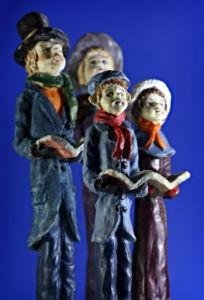 Set of old porcelain Christmas carolers on a blue background.