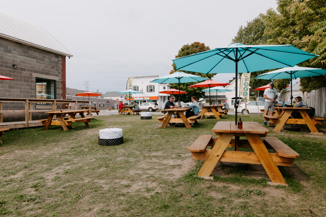 Outdoor dining area with picnic tables outside of Five Shores Brewing in Benzie County