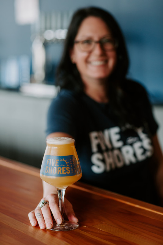 Bartender serving up a beer from Five Shores Brewing in Benzie County.