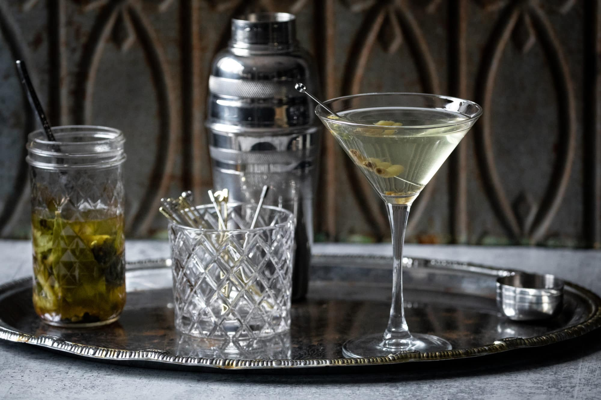 Photo of a ramp gibson on a table with a cocktail shaker, vodka and pickled ramps.