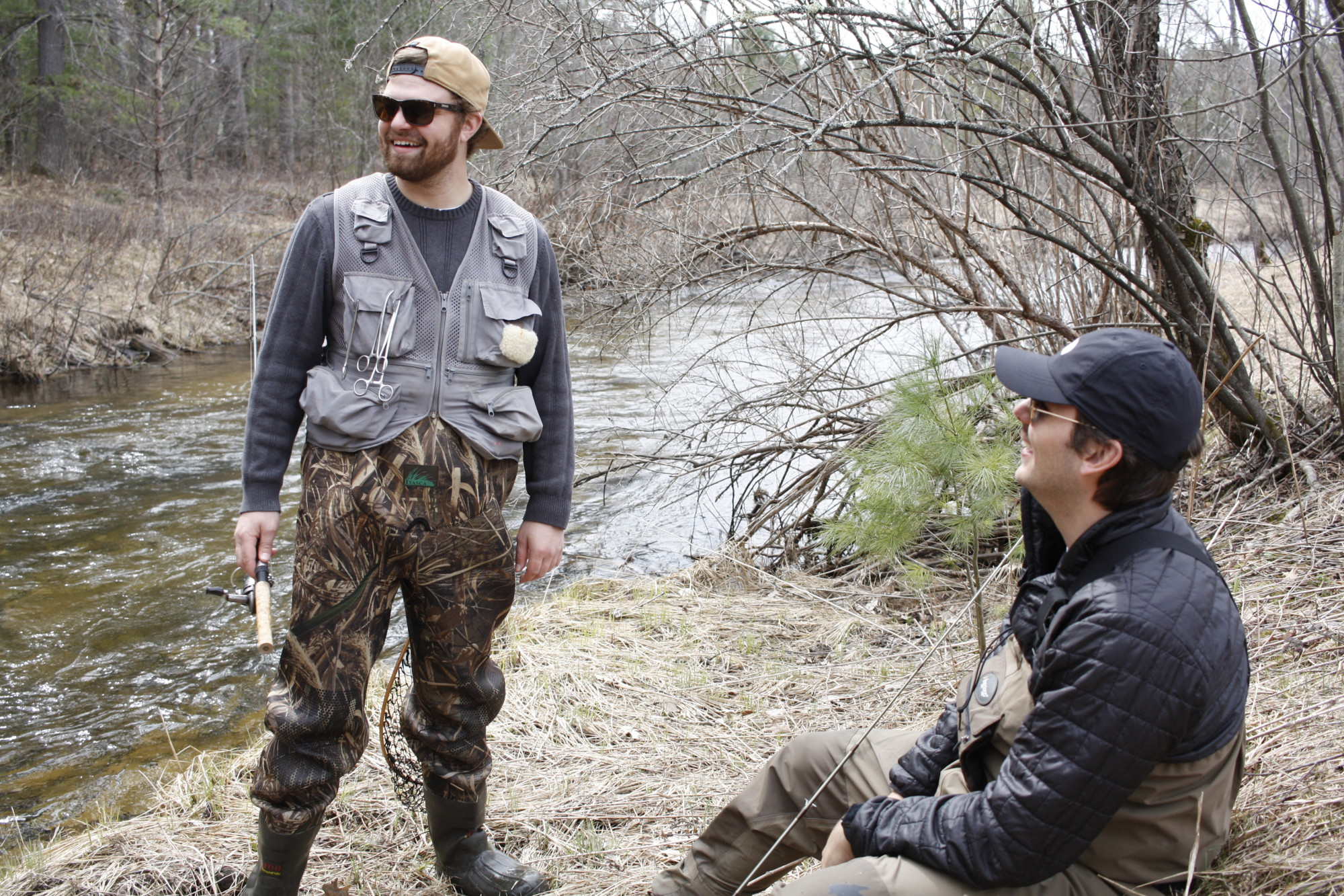Two men talking in waders getting ready to go fishing.