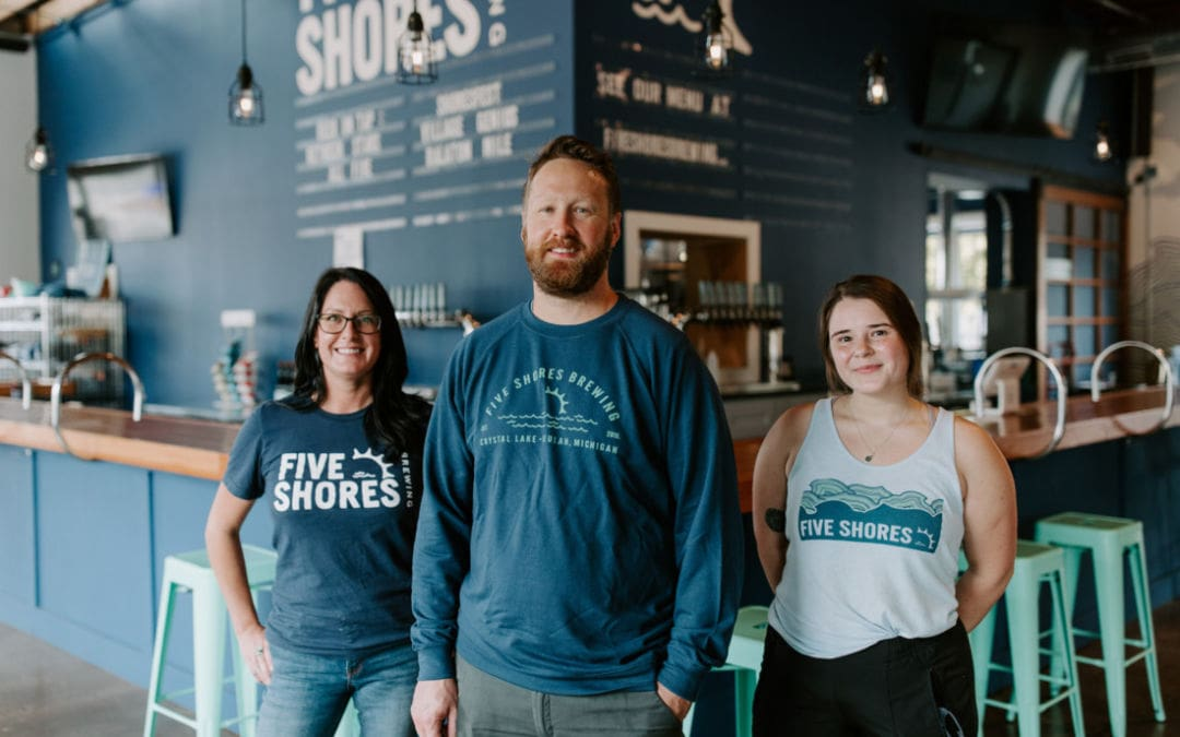 Photo of Five Shores Brewing brewmaster Oliver Roberts alongside team members at Benzie County bar.