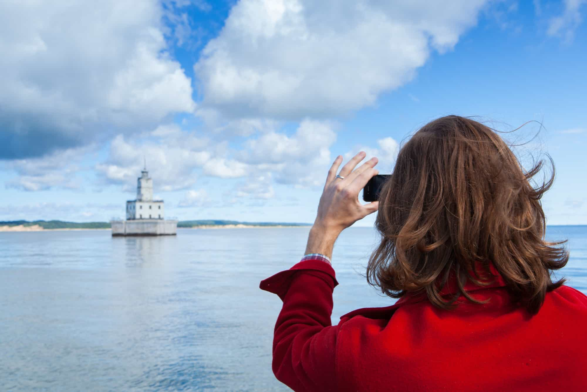 Woman taking picture of North Manitou Shoal Light in Leland.