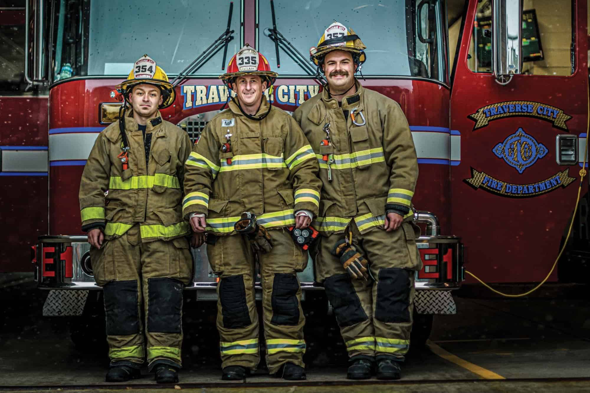 Three Traverse City firefighters in front of a firetruck.