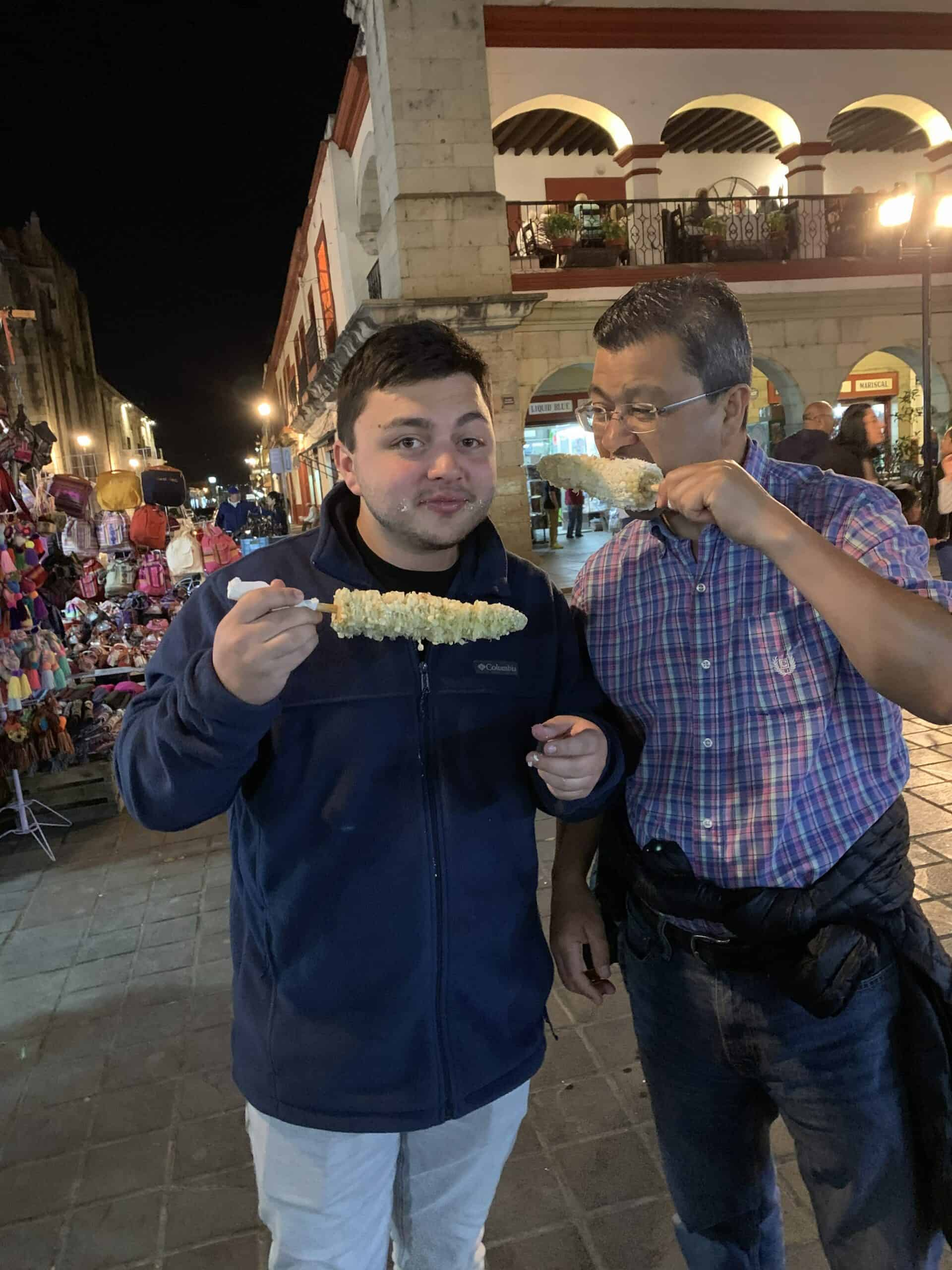 Miguel Osorio and son eating elote in Mexico.